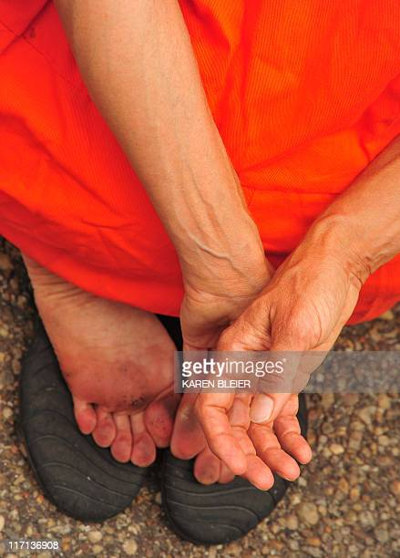 The hands and feet of a prisoner dressed in the orange jumpsuits and black hoods that are now emblematic of the policies of torture and abuse that...