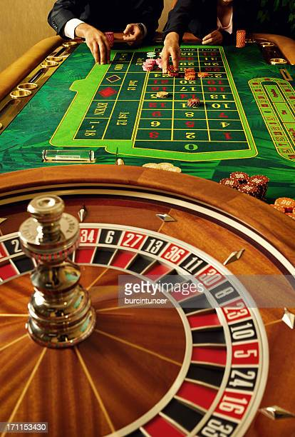 The hands and torsos of two gamblers playing casino roulette