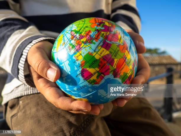 the hands of a child with a globe in his hands. ecology and globalization concept - 自然地理学 ストックフォトと画像