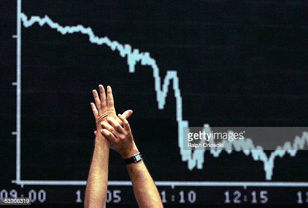 The hands of a German trader who stretches himself are seen in front of the German DAX index board on the floor of Frankfurt stock exchange on July 7...