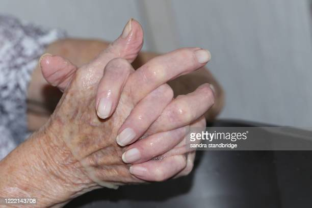 the hands of a senior lady washing her hands above a bowl of water. - care home stock pictures, royalty-free photos & images