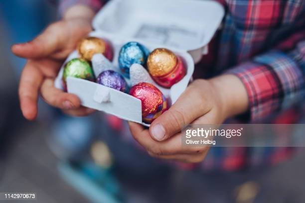 the hands of a unrecognizable little boy holding a box of chocolate easter eggs - easter egg stock pictures, royalty-free photos & images