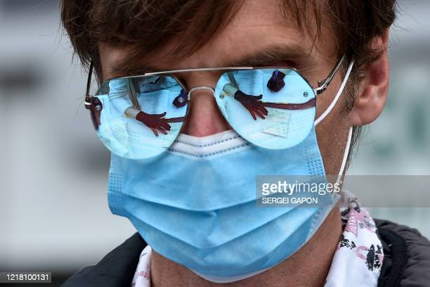 The hands of a woman collecting signatures for alternative candidates, is reflected on the glasses of a man wearing a protective face mask, on June...