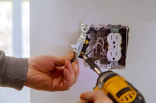 The hands of an electrician installing a power switch 1139582506