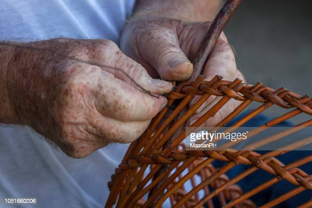 The hands of an old craftsman weave a willow basket