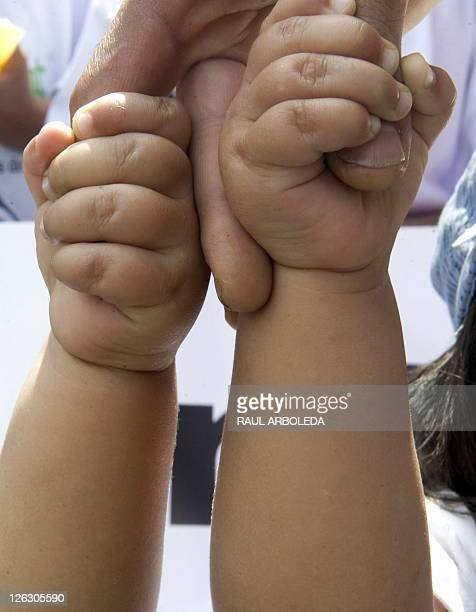 The hands of Colombian twins Juan Manuel and John Anderson Giraldo are seen during a march against infant obesity on September 24 2011 in Medellin...