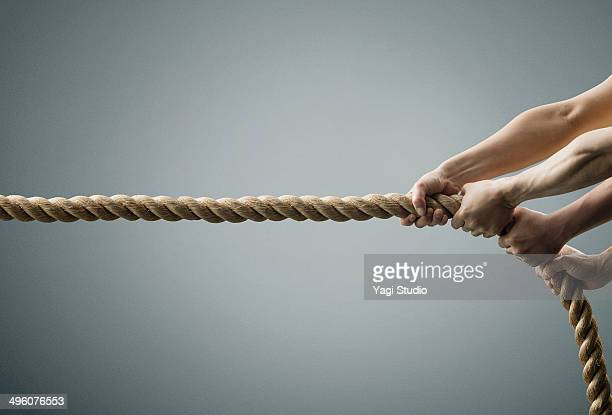the hands of two men pulling the rope - seil stock-fotos und bilder
