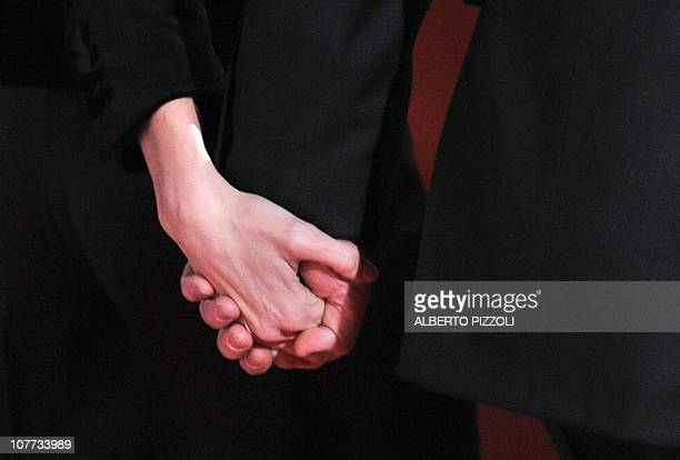 The hands of US actors Brad Pitt and Angelina Jolie pose as they arrive for the premiere of her movie The Tourist by German director Florian Henckel...