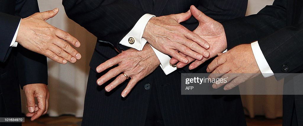 The hands of US Defense Secretary Robert Gates (C), Japan's Minister of Defense Toshimi Kitazawa (R) and South Korean Defense Minister Kim Tae Young, prepare to shake during the Shangri-La Dialogue's Asia Security Summit in Singapore on June 5, 2010. Gates chided China for suspending military ties over US arms sales to Taiwan, saying Beijing's stance 'makes little sense'. Renewing his call for stronger relations between the Chinese and US militaries, Gates said such a dialogue should not be 'held hostage' over the weapons sales. AFP PHOTO / Carolyn Kaster / POOL