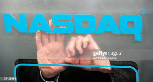 The hands of US Nasdaq Stock Market CEO Bob Greifeld are seen behind the logo as he opens its market remotely from the the World Economic Forum...