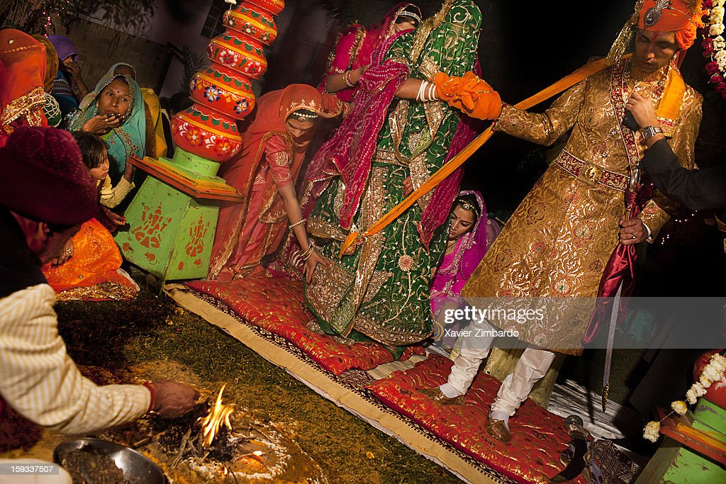 The hands tied with a scarf, the bride and the bride groom sit in front of the sacred fire lighted by the priest, a Pandit Brahmin, who commences the marriage under a canopy called chanwary that is specially decorated for the ceremony and invokes blessings of God for the couple to be married on February 18, 2011 in Barmer, Rajasthan, India.