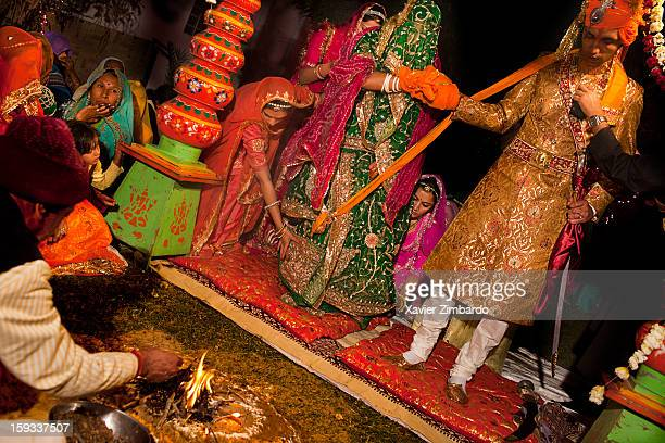 The hands tied with a scarf the bride and the bride groom sit in front of the sacred fire lighted by the priest a Pandit Brahmin who commences the...