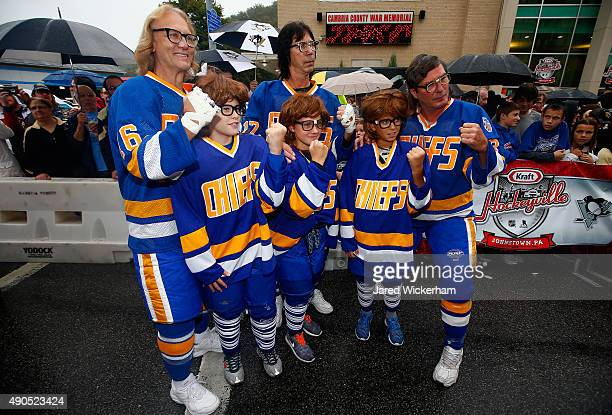 The Hanson Brothers Dave Hanson Steve Carlson and Jeff Carlson pose with young hockey fans outside the Cambria County War Memorial Arena before the...