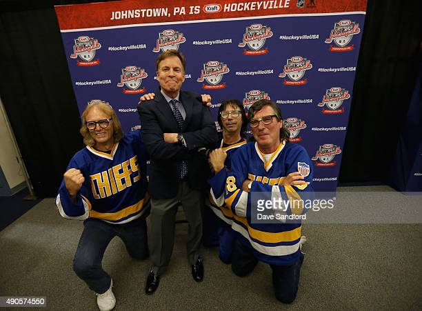 The Hanson Brothers Dave Hanson Steve Carlson and Jeff Carlson pose with sportscaster Bob Costas during the second intermission of the NHL Kraft...