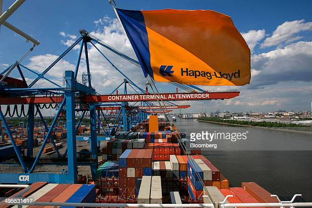 The HapagLloyd logo sits on a flag flying above shipping containers aboard the container ship Ulsan Express operated by HapagLloyd AG moored at the...
