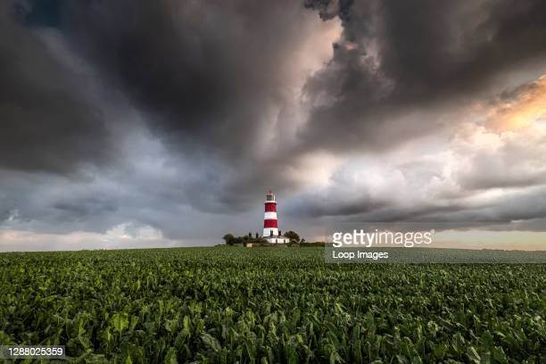 The Happisburgh lighthouse on the North Norfolk coast sat in the middle of a farmers field with storm clouds overhead.