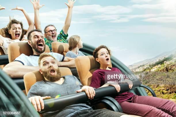 公園でローラー コースターに良い時間を持つ男性と女性の幸せの感情