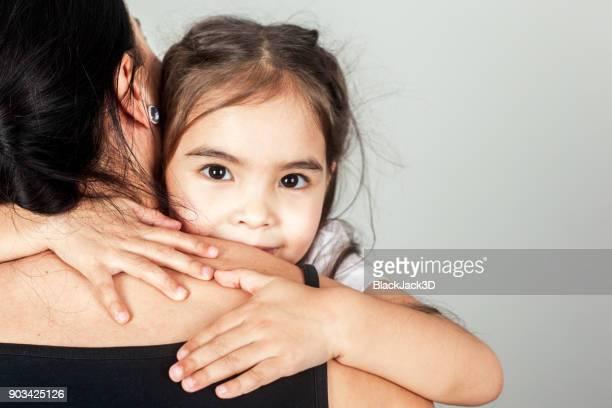 The Happy Little Girl Hugs Mom
