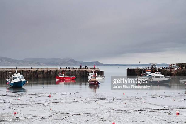 The harbour at Lyme Regis under rain clouds.