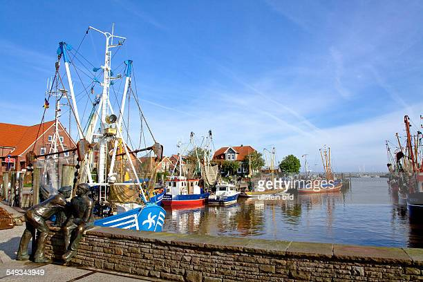 The harbour of Neuharlingersiel East Friesland at the North Sea Coast of Germany Fishing boats and a monument of fishermen