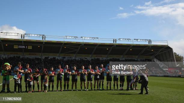 The Harlequins players participate in a minutes applause in memory of former Harlequin Sebastian AdeniranOlule the Gallagher Premiership Rugby match...
