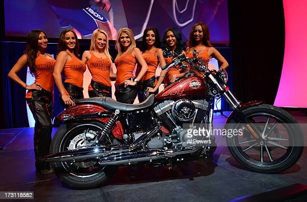 The Harley Davidson girls pose for a photo with a custom Harley Davidson motorcycle to be raffled off during the UFC Fan Expo Las Vegas 2013 at the...