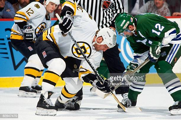 The Hartford Whalers' center Mark Johnson wins the faceoff against a Boston Bruins player during a game at the Boston Garden circa 1991 in Boston...