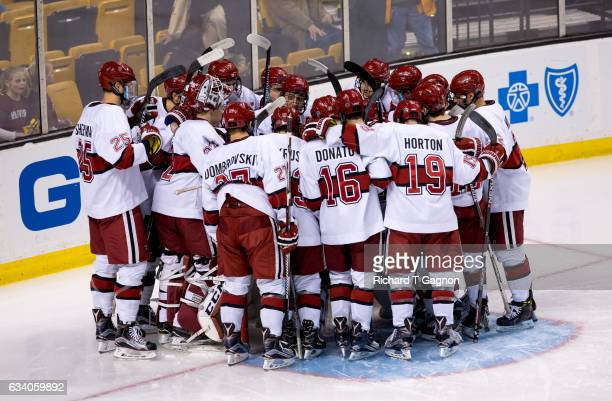 The Harvard Crimson huddle around Merrick Madsen berore NCAA hockey in the semifinals of the annual Beanpot Hockey Tournament against the...
