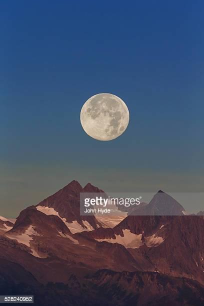 the harvest moon (september moon) rises above the chilkat mountains near juneau, southeast alaska - paisajes de alaska fotografías e imágenes de stock