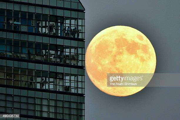 The harvest moon rises near Fukuoka Tower on September 27 2015 in Fukuoka Japan Japanese celebrate the 'harvest moon' or 'midautumn moon' on the...
