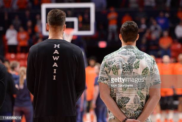 The Hawaii Rainbow Warriors logo is seen on the back of a players warm up shirt as he stands next to a team manager that wears an Aloha Shirt before...