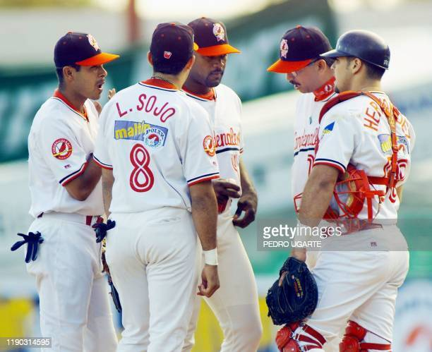 The head coach for the Cardenales de Lara of Venezuela Omar Malave speaks to starting pitcher Kelvin Escobar as other team members look on after...