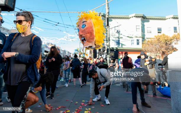 The head of a Donald Trump pinata hangs above as people collect candy that fell out of it while they celebrate Joe Biden being elected President of...