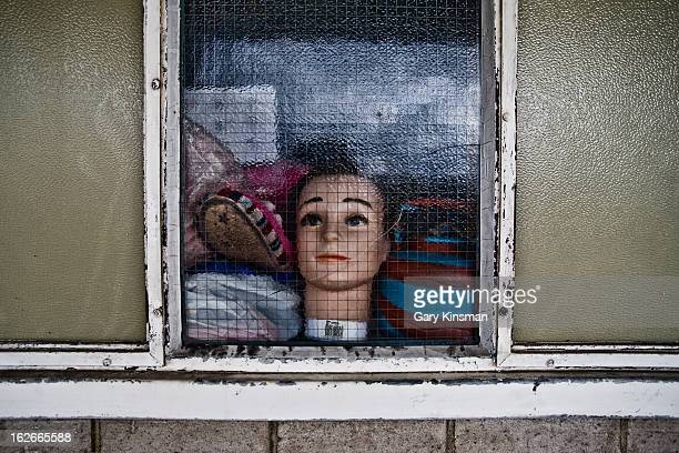 The head of a mannequin seen through the window on the abandoned Heygate Estate in Elephant & Castle, South London, 2009