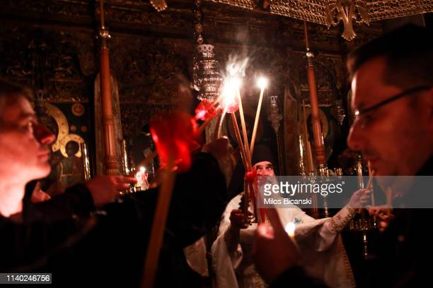 The head of a Osiou Gregoriou monastery Igumen Christophoros pass the Holy flame to Orthodox Christian worshippers during the Easter Sunday Mass at...
