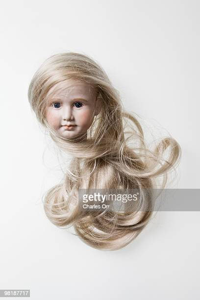The head of a porcelain doll with long blond hair