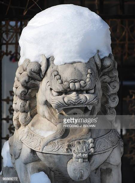 The head of a stone lion is covered in snow in Beijing on January 4 2010 Two days of heavy snow in north China led to schools being shutdown flights...