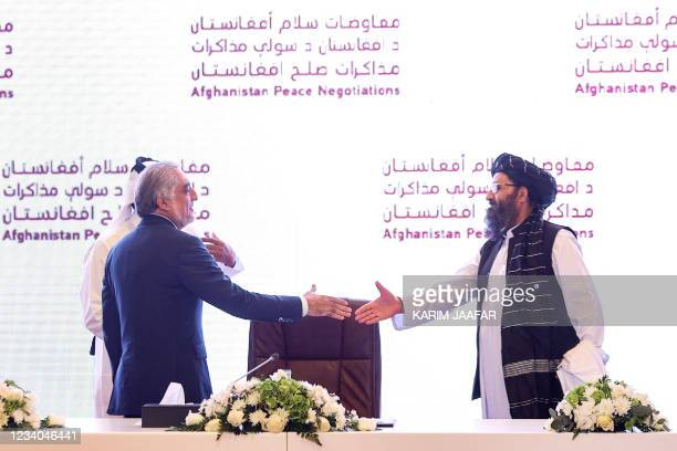 The head of Afghanistan's High Council for National Reconciliation Abdullah Abdullah prepares to shake hands with the leader of the Taliban...