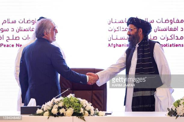 The head of Afghanistan's High Council for National Reconciliation Abdullah Abdullah shakes hands with the leader of the Taliban negotiating team...