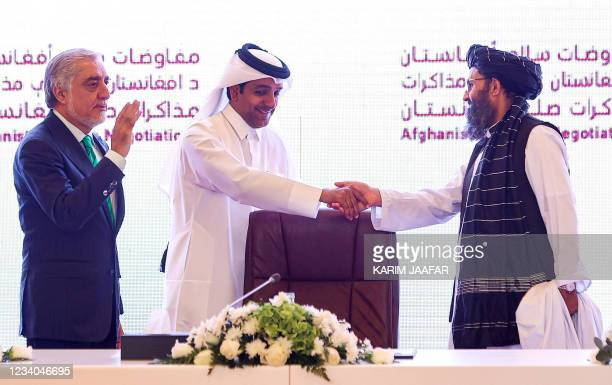 The head of Afghanistan's High Council for National Reconciliation Abdullah Abdullah gestures as Qatar's envoy on counter-terrorism Mutlaq al-Qahtani...