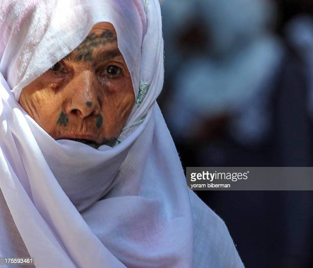 The head of an old woman, covered with a white veil , and decorated with a very special tattoo.