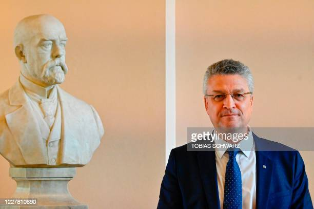 The head of Germany's Robert Koch Institute , Lothar Wieler, poses next to the bust of Robert Koch after addressing a news conference on the...