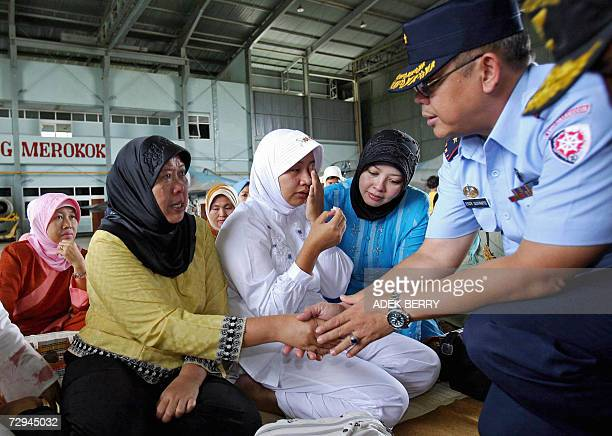 The head of Indonesia's search and rescue operation Eddy Suyanto shakes hands with the mother of Adam Air flight attendant Rusmala Dewi after a group...