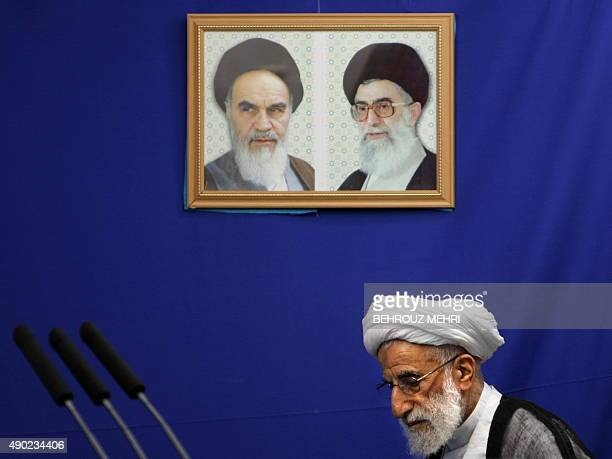 The head of Iran's electoral body the Guardians Council Ahmad Jannati stands under the portraits of Iran's late founder of Islamic Republic Ayatollah...