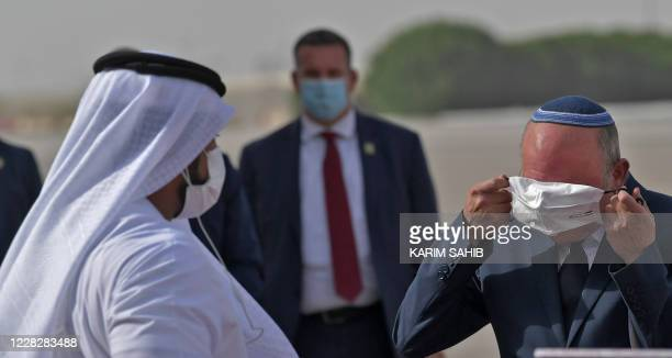 The Head of Israel's National Security Council, Meir Ben-Shabbat, puts on a facemask to avoid the spread of the Covid-19 coronavirus, at the tarmac...