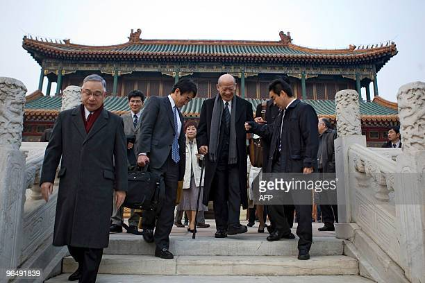 The head of Japan's delegation Taizo Nishimuro is helped down the stairs following his meeting with Chinese Premier Wen Jiabao as part of the...