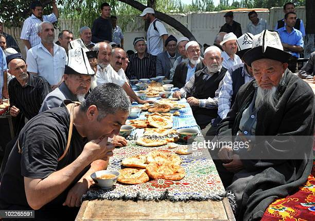 The head of local police, colonel Kursan Asanov eats with Ethnic Uzbek after a peace rally to call on ethnic Uzbeks to pull down a barricade between...