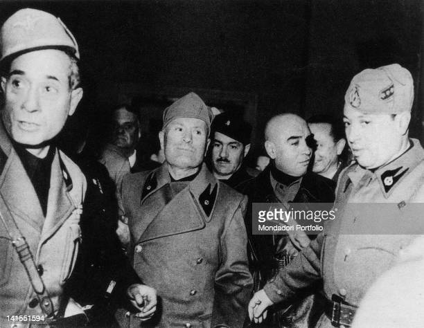 The head of the Fascist government Benito Mussolini leaving the Teatro Lirico alongside the Secretary of the Fascist party Alessandro Pavolini and...