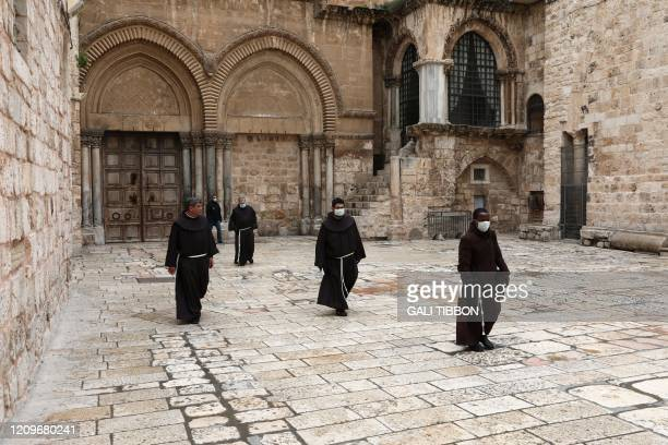 The head of the Franciscan order in the Holy Land, or Custos, and three friars walk in the yard of the Church of the Holy Sepulchre in Jerusalem's...