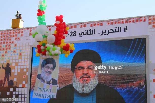 The head of the Lebanese Shiite movement Hezbollah Hasan Nasrallah is seen delivering a televised speech to his supporters as they attend on August...